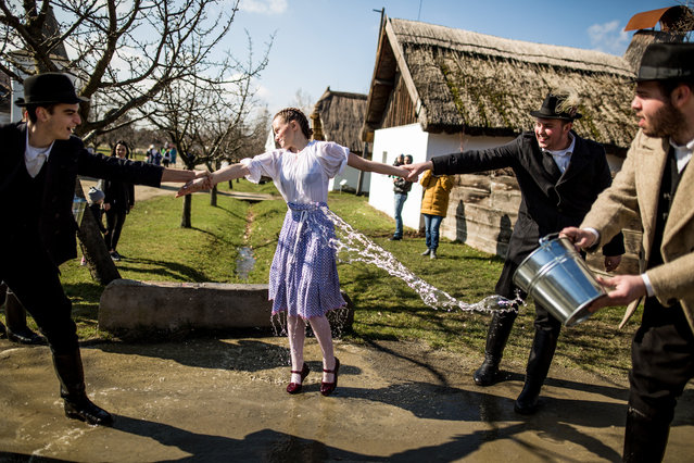 Members of the Mayossa folk dance group pour water on a young woman in Kiskunmajsa, Hungary on April 2, 2018. According to an old Hungarian tradition, celebrated for several hundred years, young men pour water on young women, who in exchange present their sprinklers with beautifully colored eggs on Easter Monday. (Photo by Mudra László/Origo Photo)