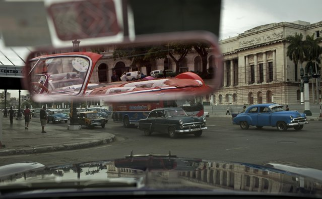 In this October 16, 2014 photo, people drive classic American car in Old Havana, Cuba. These classic cars are now part of Havana's tourist draw. That's allowed many to paint and polish their aging vehicles. (Photo by Franklin Reyes/AP Photo)