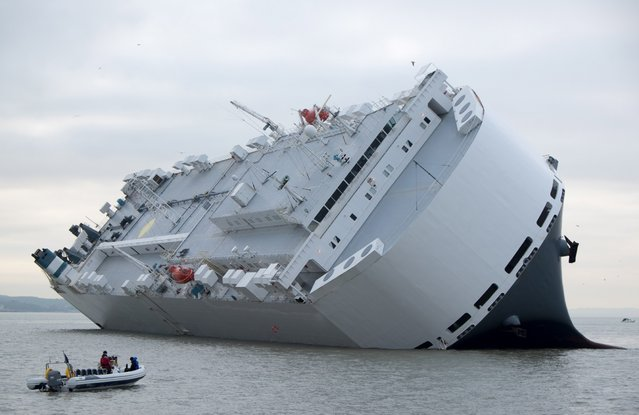 A small boat sails past the Hoegh Osaka car transporter cargo ship that ran aground in the Solent, off the Isle of Wight Sunday January 4, 2015. The crew members of the Hoegh Osaka were taken to safety by a coastguard helicopter and lifeboats after it became stranded on Bramble Bank, in the Solent between Southampton and the Isle of Wight. (Photo by AP Photo/Francis Bigg Photography)