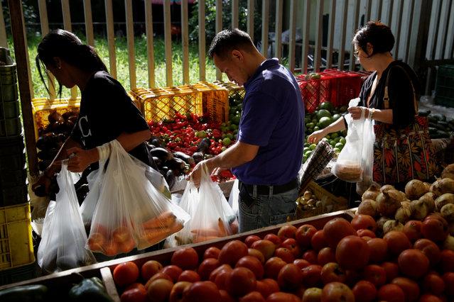 People buy vegetables at a market in Caracas, Venezuela October 28, 2016. (Photo by Marco Bello/Reuters)