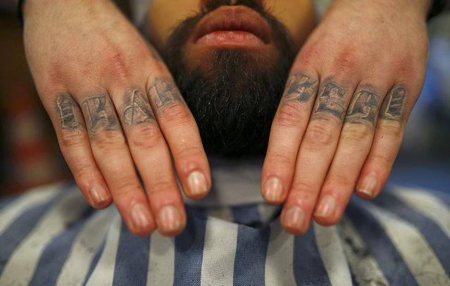 "Alex ""Torreto"" Vellios, a 26-year old barber displays his tattoo reading ""barber"" as he massages a conditioning oil into the beard of his assistant Sam at his Torreto barber shop in Frankfurt January 6, 2015. (Photo by Kai Pfaffenbach/Reuters)"