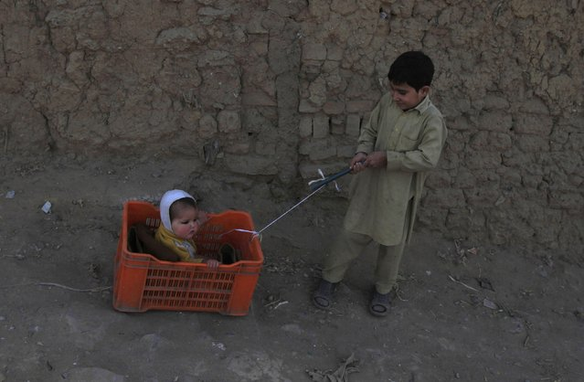 A boy plays with his brother as he sits in a crate at a slum on the outskirts of Islamabad January 6, 2015. (Photo by Faisal Mahmood/Reuters)