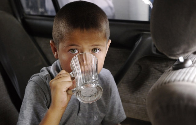 """A boy drinks a glass of water given him by his grandmother on a 108F (42C) day. According to one guidebook """"only the insane or deeply unfortunate"""" end up in Ashgabat in the hottest months of July and August. (Photo by Amos Chapple via The Atlantic)"""