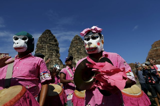 People wears masks of monkeys at the Pra Prang Sam Yot temple before the annual Monkey Buffet Festival in Lopburi, north of Bangkok November 29, 2015. (Photo by Jorge Silva/Reuters)