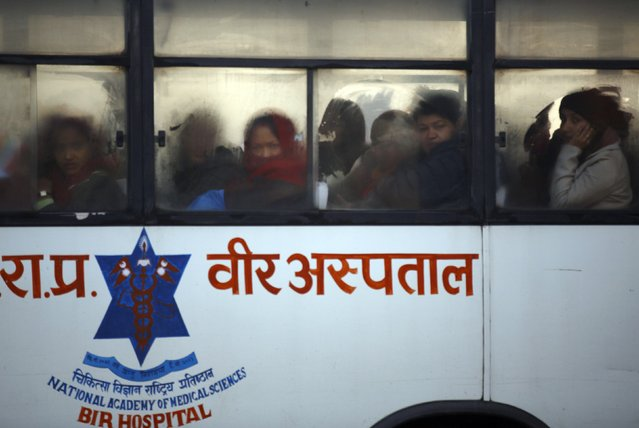 Hospital staff heading towards the hospital looks towards protesters from a bus during the general strike independently called by the Unified Communist Party of Nepal (Maoist) and led by 30 party alliance and the Communist Party of Nepal (Maoist), demanding that the drafting of the new constitution is done on time through consensus, in Kathmandu January 13, 2015. (Photo by Navesh Chitrakar/Reuters)