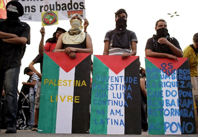 Demonstrators use makeshift shields painted with the colours of the Palestinian flag during a protest against fare hikes for city buses in Rio de Janeiro January 16, 2015. (Photo by Mauro Pimentel/Reuters)