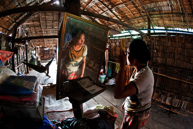 """My Old Home"". The interior home of one of the outback villages in the outskirts of Siem Reap, Cambodia is as simple as it can be, devoid of much luxuries and necessities, as can be seen in the home of this Cambodia lady making herself up before she starts her day. (Photo and caption by Nick Ng Yeow Kee/National Geographic Traveler Photo Contest)"