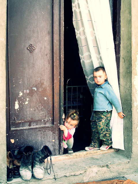 """Curiosity..."" Once I decided to take some photos, which would reflect the day-life of children, living in, simply saying, bad conditions in children's' homes. So, in one of such homes, near the capital of Georgia, Tbilisi, when I was talking to the director of the home, this little sweethearts came out and starting to examine the situation. The boy stared at me for a second and suddenly ran away to hug her mother, sitting near. Meanwhile, boy's little sister, wondering what was happening outside, half-standing on her knees, was curiously involved in something that only she could understand that moment. (Photo and caption by Natalia Burduli/National Geographic Traveler Photo Contest)"