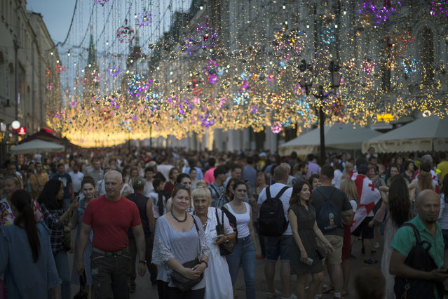 Muscovites, tourists and soccer fans walk through Nikolskaya Street, a favorite meeting place for fans from different countries, during the 2018 soccer World Cup in Moscow, Russia, Saturday, June 23, 2018. (Photo by Alexander Zemlianichenko/AP Photo)