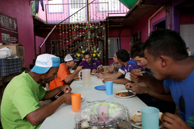 "Immigrants eat at the premises of a group called ""Las Patronas"" (The bosses), a charitable organization that feeds Central American immigrants on their way to the border with the United States who travel atop a freight train known as ""La Bestia"", in Amatlan de los Reyes, in Veracruz state, Mexico October 22, 2016. (Photo by Daniel Becerril/Reuters)"