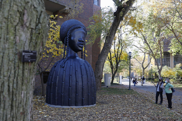 People look at a newly installed sculpture by artist Simone Leigh on the University campus in Philadelphia, Tuesday, November 10, 2020. Leigh's 16-foot-tall bronze bust of a Black woman has been installed at the entrance to the heart of the University of Pennsylvania's campus. (Photo by Rebecca Blackwell/AP Photo)
