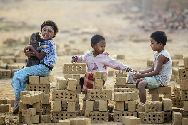 Children play on bricks while their parents work at a brick kiln on the outskirts of Yangon February 1, 2015. (Photo by Soe Zeya Tun/Reuters)