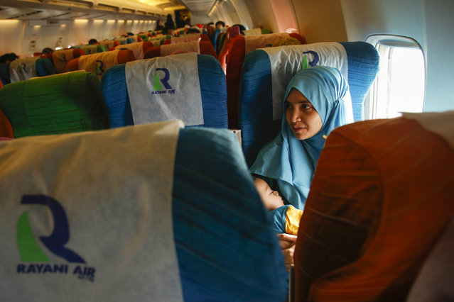 In this December 22, 2015, photo, a Muslim woman passenger comforts her baby on board the Rayani Air after departure from Kuala Lumpur International Airport 2 in Sepang, Malaysia. (Photo by Joshua Paul/AP Photo)