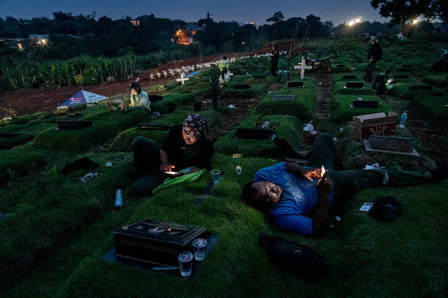 Shortlist, open competition, street photography. Night in Pandemic Time, taken at the Pondok Ranggon Cemetery, Jakarta, late one afternoon. The funeral officers were having a break, watching videos on their smartphones and chatting with their families. (Photo by Ares Jonekson Saragi/Sony World Photography Awards)