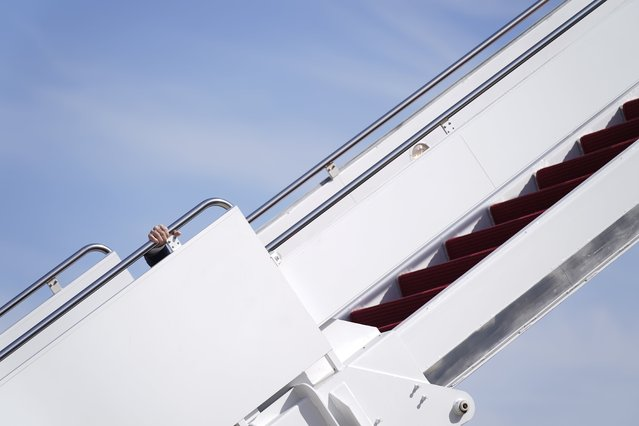 President Joe Biden holds onto the hand rail as he stumbles while boarding Air Force One at Andrews Air Force Base, Md., Friday, March 19, 2021. Biden is en route to Georgia. (Photo by Patrick Semansky/AP Photo)