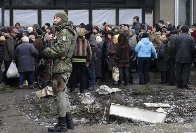 Soldier stands guard as humanitarian aid is distributed to residents in the town of Debaltseve, Ukraine, Friday, February 6, 2015. (Photo by Petr David Josek/AP Photo)