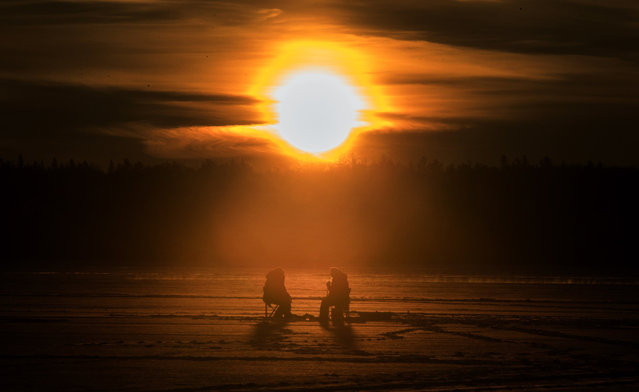 Anglers from Curve Lake First Nations bring in the dawn, ice fishing on Pigeon Lake in central Ontario's Kawartha Lakes, Sunday January 24, 2021. (Photo by Fred Thornhill/The Canadian Press via AP Photo)