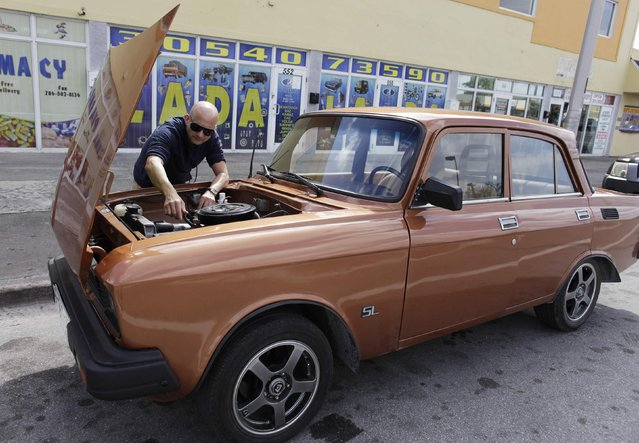 Lester Luis checks a Moskvich in front of Fabian Zakharov's Zakharov Auto Parts shop in Hialeah, Florida, February 4, 2015. (Photo by Javier Galeano/Reuters)
