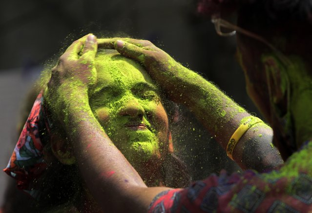 Indians smear colored powder on each other during Holi festival in Mumbai, India, Monday, March 29, 2021. (Photo by Rajanish Kakade/AP Photo)