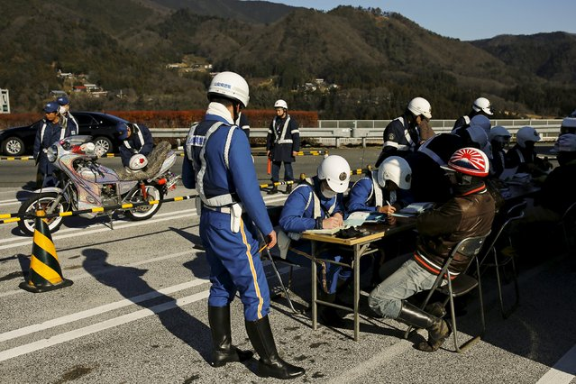 Policemen hand out penalties to Bousouzoku bikers for illegal customisation of their motorcycles at the Dangouzaka rest stop in Yamanashi, west of Tokyo, Japan, January 3, 2016. (Photo by Thomas Peter/Reuters)