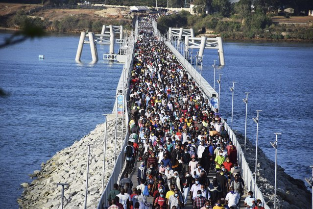 Some hundreds of Mombasa residents cross the recently constructed floating foot bridge from Mombasa's Likoni mainland to the Mombasa Island on Wednesday March 31, 2021. More than three hundred thousand people who normally cross the waterway via Likoni Ferry channel everyday, are now forced to use the floating foot bridge after the Mombasa County Covid-19 committee ordered all people to cross via the bridge. It is not exactly known how many people the floating bridge can sustain and some fear a disaster due to the high number of people crossing through the bridge. (Photo by Gideon Maundu/AP Photo)