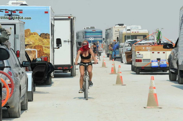 In this Aug. 26, 2013 photo, a woman rides her bike between cars waiting to enter Burning Man in Gerlach, Nev. According to The Reno Gazette-Journal, an estimated 68,000 people are anticipated to attend the event. (Photo by Andy Barron/AP Photo/Reno Gazette-Journal)
