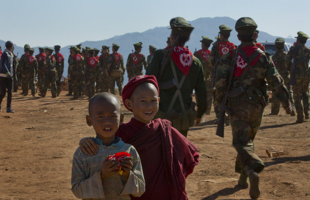 In this January 12, 2015 photo, a novice Buddhist monk and a boy smile as Ta'ang National Liberation army officers walk back to their jungle camps after a celebration in Mar Wong Village, northern Shan state, Myanmar, marking their insurrection more than a half-century ago. (Photo by Gemunu Amarasinghe/AP Photo)