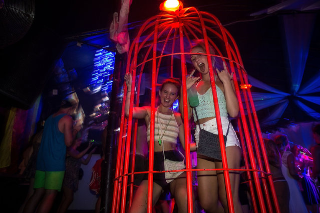 """Girls dance in a cage in a nightclub during Australian """"schoolies"""" celebrations following the end of the year 12 exams in a nightclub on November 25, 2013 in Kuta, Indonesia. Every year over 3000 students descend on destinations such as Bali, Thailand, Fiji and Cambodia to celebrate """"Schoolies Week"""", which marks the end of the school year. Destinations such as Kuta in Bali are often chosen because of cheap alcohol and all night parties. (Photo by Agung Parameswara/Getty Images)"""