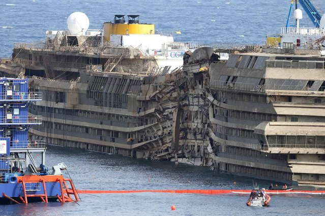 "The Costa Concordia is seen after it was lifted upright, on the Tuscan Island of Giglio, Italy, Tuesday, September 17, 2013. The crippled cruise ship was pulled completely upright early Tuesday after a complicated, 19-hour operation to wrench it from its side where it capsized last year off Tuscany, with officials declaring it a ""perfect"" end to a daring and unprecedented engineering feat. (Photo by Andrea Sinibaldi/AP Photo/Lapresse)"