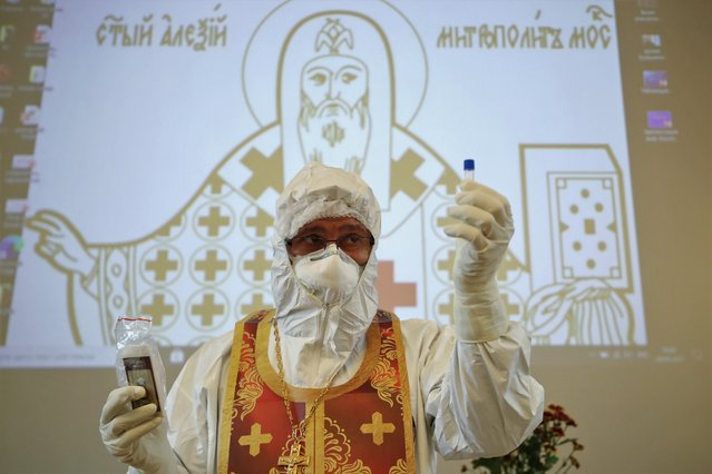 """Archpriest Ioann Kudryavtsev shows a disposable vial of consecrated oil during his lecture titled """"Pastoral Counselling Amid the Pandemic – PPE Use and Spiritual Guidance of COVID-19 Patients"""" at St Alexy Hospital Metropolitan of Moscow Hospital as part of a five-day course on spiritual care of red zone COVID-19 patients in Moscow, Russia on April 20, 2021. (Photo by Mikhail Tereshchenko/TASS)"""