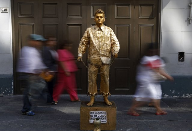 A boy impersonating a living statue performs for tips in downtown Lima, February 19, 2015. (Photo by Mariana Bazo/Reuters)