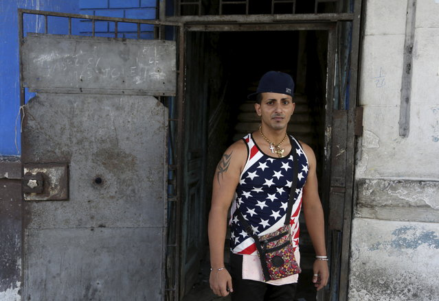Yasiel, 28, wearing a shirt with the U.S flag, stands on a street in Havana July 2, 2015. (Photo by Alexandre Meneghini/Reuters)