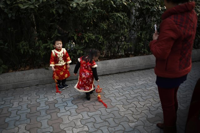 A boy, dressed in traditional Chinese clothes, reacts as his grandmother tries to take a picture of him and his sister with a mobile phone, on a busy street in downtown Shanghai, February 12, 2015. (Photo by Carlos Barria/Reuters)