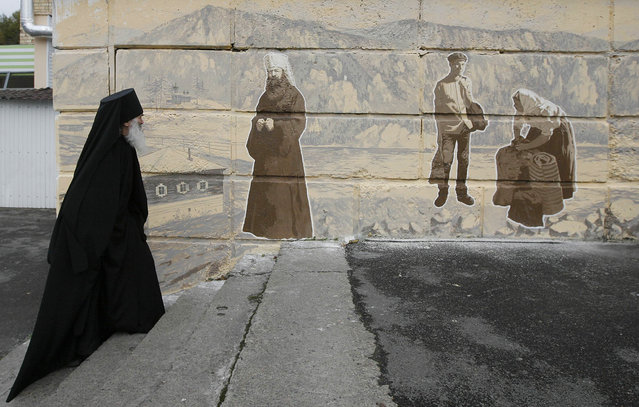 Orthodox monk Father Ioakim, 74, looks at a street graffiti, which displays Siberian characters of the 19th century including an Russian Orthodox monk, in Divnogorsk town outside Russia's Siberian city of Krasnoyarsk, September 30, 2013. The monk from a local parish came to the place to look at the artwork created by an unknown author and telling a story about an Orthodox priory which was replaced by the town for builders of Krasnoyarsk hydroelectric station in the middle of the 20th century and now called Divnogorsk town. (Photo by Ilya Naymushin/Reuters)