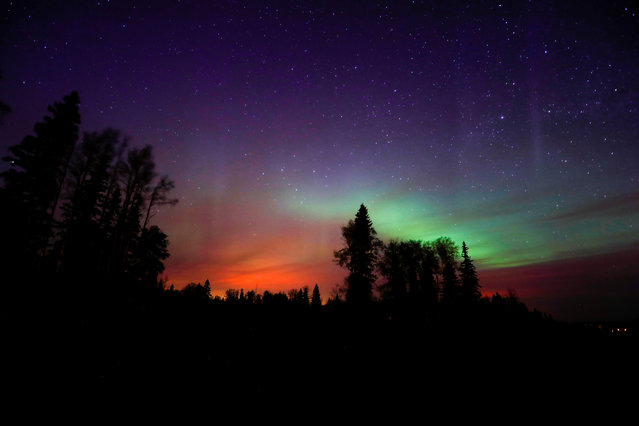 The wildfires glow underneath The Northern Lights, also known as the Aurora Borealis, near Fort McMurray, Alberta, Canada, May 7, 2016. (Photo by Mark Blinch/Reuters)