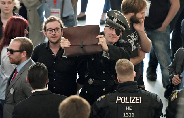 Martin Sonneborn, member of the European Parliament is dressed in a mock-up uniform of Germany's Third Reich army Wehrmacht as he is blocked by security and police to enter a book presentation of Bjoern Hoecke of Germany's Alternative for Germany AFD party at the Frankfurt Book Fair in Frankfurt, Germany, October 12, 2018. (Photo by Thorsten Wagner/Reuters)