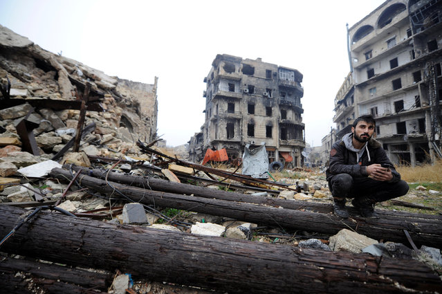 A man sits amid debris near Umayyad mosque, in the government-controlled area of Aleppo, during a media tour, Syria December 13, 2016. (Photo by Omar Sanadiki/Reuters)