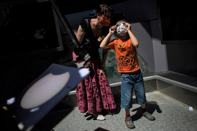 A woman with child observes the partial solar eclipse with special glasses as projection of eclipse from telescope is seen in front, at observatory in Prague, Czech Republic, 10 June 2021. A partial solar eclipse occurs when a portion of the Earth is engulfed by the shadow (penumbera) cast by the Moon as it passes between our planet and the Sun in an imperfect alignment. (Photo by Martin Divísek/EPA/EFE)