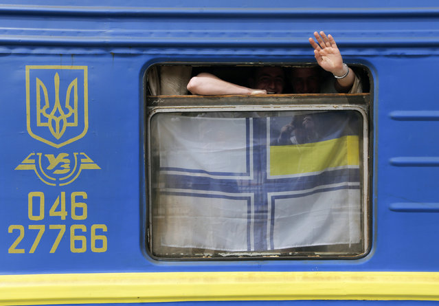 Ukrainian servicemen wave out of a car window decorated with Ukrainian Navy flag prior to their departure to the Black Sea port of Odessa at the railway station in Sevastopol, April 6, 2014. (Photo by Maxim Shemetov/Reuters)