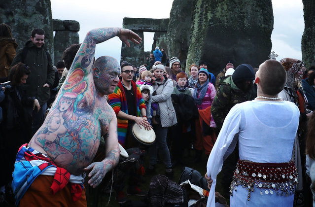Solstice reveller Mad Al dances as druids, pagans and revellers gather in the centre of Stonehenge, hoping to see the sun rise, as they take part in a winter solstice ceremony at the ancient neolithic monument of Stonehenge near Amesbury on December 21, 2016 in Wiltshire, England. (Photo by Matt Cardy/Getty Images)