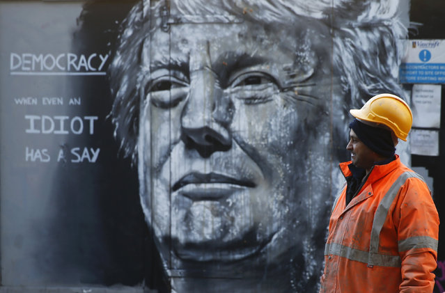 A construction worker stands in front of a piece of street art portraying prospective U.S. Presidential candidate Donald Trump, in east London, January 28, 2016. An online petition to bar Trump from entering the United Kingdom recently triggered a debate in Parliament after if was signed by over 500,000 people. (Photo by Andrew Winning/Reuters)