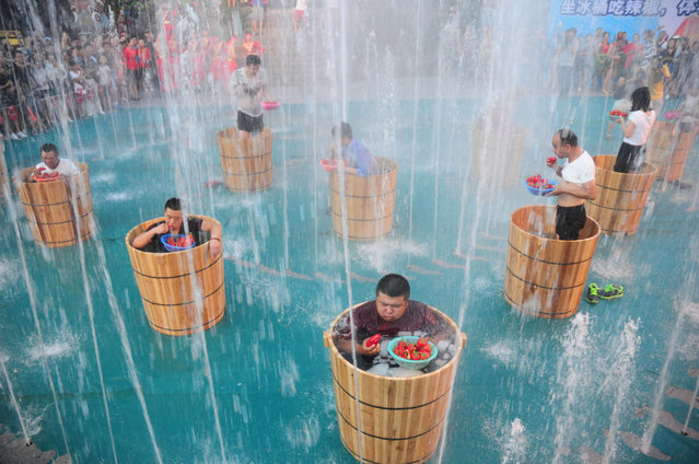 Tourists sitting in the ice buckets eat peppers in the fountain during a competition at Song Dynasty Town on July 20, 2016 in Hangzhou, Zhejiang Province of China. As the ground temperature reached 40 degrees Celsius in Hangzhou, tourists competed eating peppers while sitting in the ice buckets to feel hot and cool at the same time in the Song Dynasty Town scenic area. (Photo by VCG/VCG via Getty Images)
