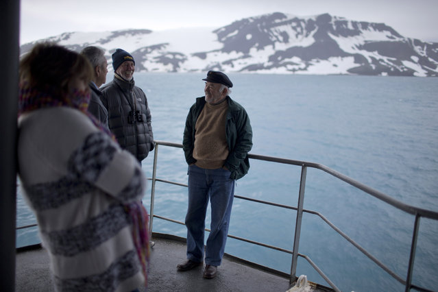 In this January 27, 2015 photo, tourists stand on The Aquiles, a Chilean Navy icebreaker, near Bahia Almirantazgo, Livingston Island, South Shetland Island archipelago, Antarctica. Although many tourists are nature-loving retirees who mostly stay aboard cruise ships, conservationists worry about potentially devastating environmental damage from boat pollution and from the more adventurous visitors who hike or cross-country ski around sensitive sites. (Photo by Natacha Pisarenko/AP Photo)