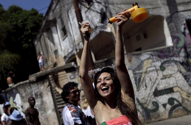 """A reveller holds up a spray representing an insecticide against the Aedes aegypti mosquito, as she takes part in an annual block party known as """"Ceu na Terra"""" (Heaven on Earth), one of the many pre-carnival parties to take place in the neighbourhoods of Rio de Janeiro, Brazil, January 30, 2016. (Photo by Ricardo Moraes/Reuters)"""