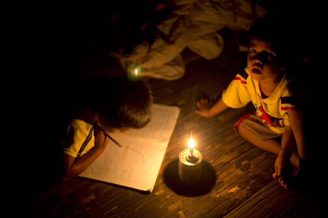In this March 16, 2015 photo, Pedro Tello draws for fun in his notebook as his younger brother Felix hangs out with him inside their home, illuminated by a candle on a tin can, serving as a makeshift candle holder, in the Ashaninka Indian hamlet of Saweto, Peru. Both boys attend school in the same one-room hut. (Photo by Martin Mejia/AP Photo)