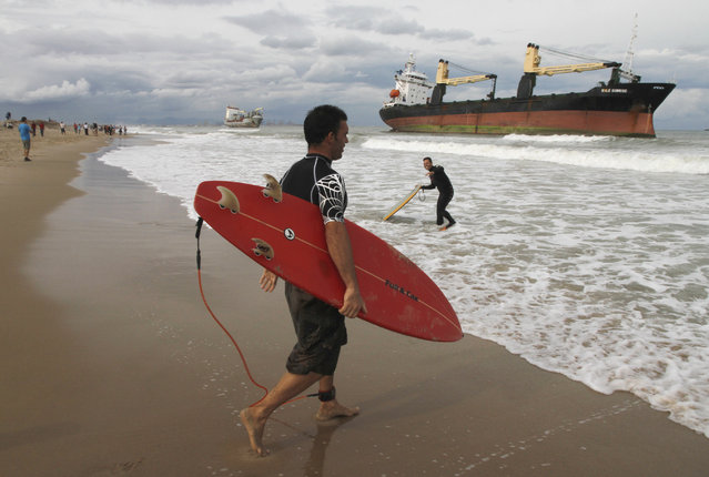 Surfers enter the water at the shore where two cargo ships lie stranded after a heavy rainstorm in Valenica, Spain, September 29, 2012. (Photo by Heino Kalis/Reuters)