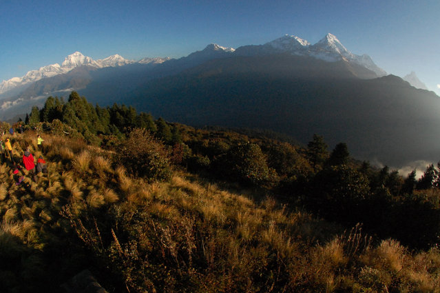 In this Friday, October 24, 2014 file photo, trekkers watch the sun rise over the Annapurna Range, right, in central Nepal, as viewed from Poon Hill, above the village of Ghorepani. A Finnish climber and his local guide died Wednesday, March 25, 2015, while descending from the summit of Mount Annapurna in the first casualties of this mountaineering season, a Nepal mountaineering official said. (Photo by Malcolm Foster/AP Photo)
