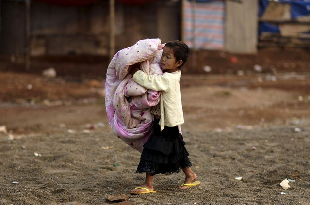 A girl holds a quilt at a refugee camp at Myanmar's border town with China, in Kokang March 24, 2015. Picture taken March 24, 2015. (Photo by Wong Campion/Reuters)