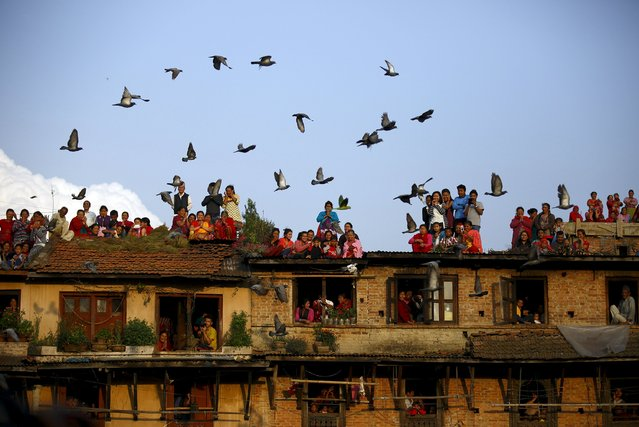 Pigeons fly past devotees gathering on the roof of the houses to observe religious rituals of Rato Machhindranath at Bungamati in Lalitpur April 5, 2015. Rato Machhindranath is known as the god of rain and both Hindus and Buddhists worship Machhindranath for good rain to prevent drought during the rice harvest season. (Photo by Navesh Chitrakar/Reuters)