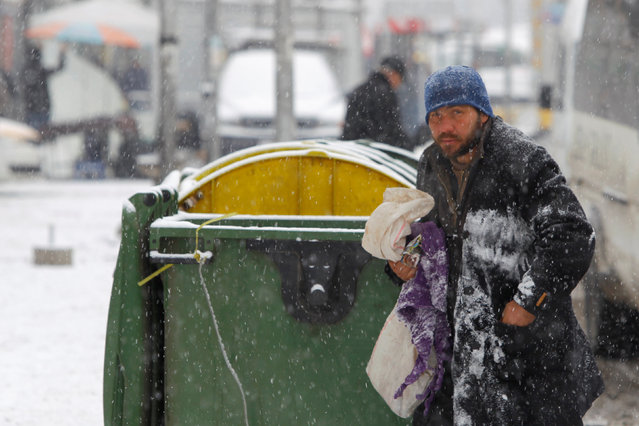 A homeless man searches for warm clothing during a snowstorm in Skopje, Macedonia January 10, 2017. (Photo by Ognen Teofilovski/Reuters)